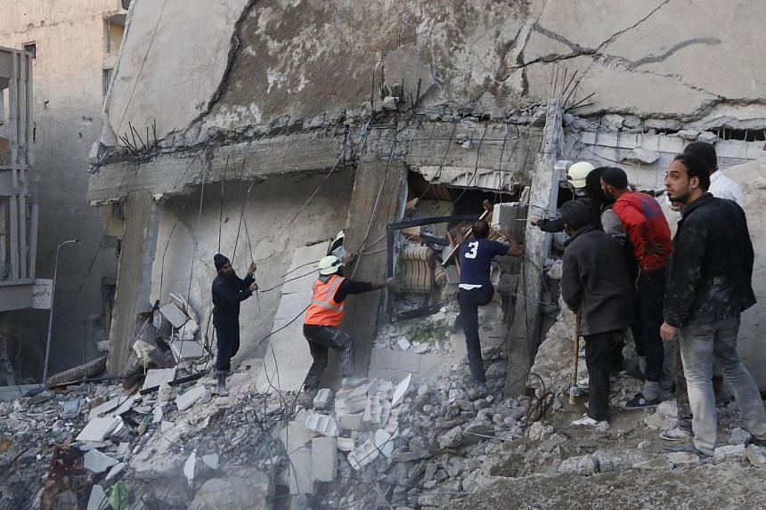 Civilians and Civil Defence members work at a site hit by airstrikes allegedly by forces loyal to Syria's President Bashar al-Assad in Raqqa, Syria, which is controlled by the Islamic State in Iraq and Syria (ISIS) on Nov 11, 2014.US President