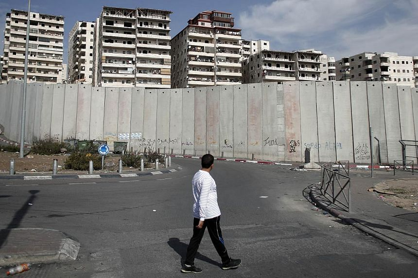 A Palestinian man walks past Israel's controversial separation barrier surrounding buildings of the Shuafat refugee camp in East Jerusalem on Nov 14, 2014.Israel will never agree to limit its construction activity in annexed east Jerusalem, For