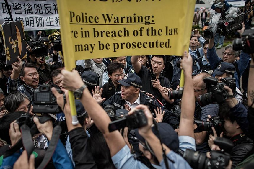 Demonstrators march towards the police headquarters, a day after the arrest of volunteer marshalls at a protest site, in the Admiralty district of Hong Kong on Nov 13, 2014. A Hong Kong court notice ordering the eviction of democracy demonstrato