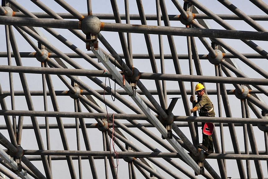 A worker welds steel bars during construction of the roof of a new railway station in Urumqi, Xinjiang Uighur Autonomous region on Oct 12, 2014. China opened the first stretch of a new high-speed railway in the western region of Xinjiang on Sund