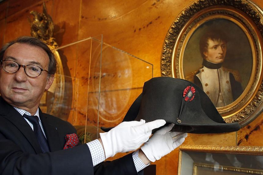 Auctioneer Jean-Pierre Osenat displays a black felt two-cornered hat belonging to French Emperor Napoleon Bonaparte at their auction house in Paris on Oct 24, 2014.-- PHOTO: REUTERS