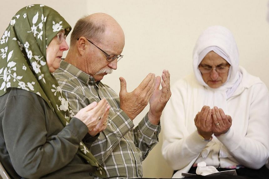 Ed Kassig, along with Habibe Ali (right) and Paula Kassig, pray for his captive son Abdul-Rahman Kassig during a prayer service honouring his humanitarian work in Syria at the Islamic Society of North America mosque in Plainfield, Indiana on Oct 10,