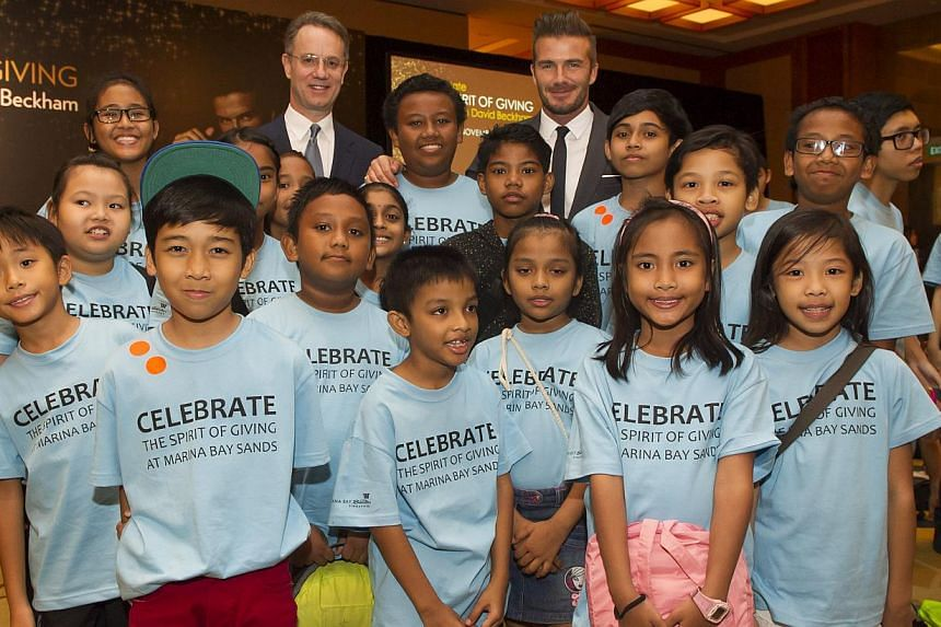 Mr. George Tanasijevich, President and Chief Executive Officer of Marina Bay Sands and David Beckham with Sands for Singapore beneficiaries. --  PHOTO: MARINA BAY SANDS