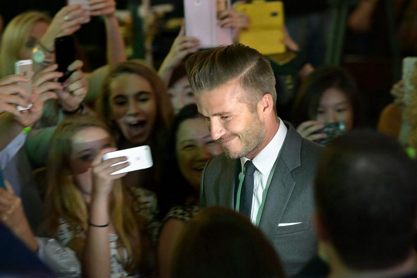 David Beckham is greeted by fans as he arrives at the Marina Bay Sands Skating Rink for the launch of the Christmas light up for Marina Bay Sands on Nov 15, 2014. -- ST PHOTO: KUA CHEE SIONG