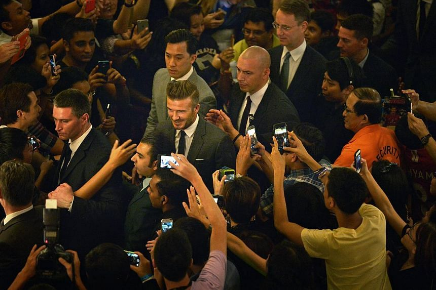 Fans of David Beckham asking for autographs and taking his picture as he takes his leave after launching the Christmas light up for Marina Bay Sands at the skating rink. -- ST PHOTO: KUA CHEE SIONG