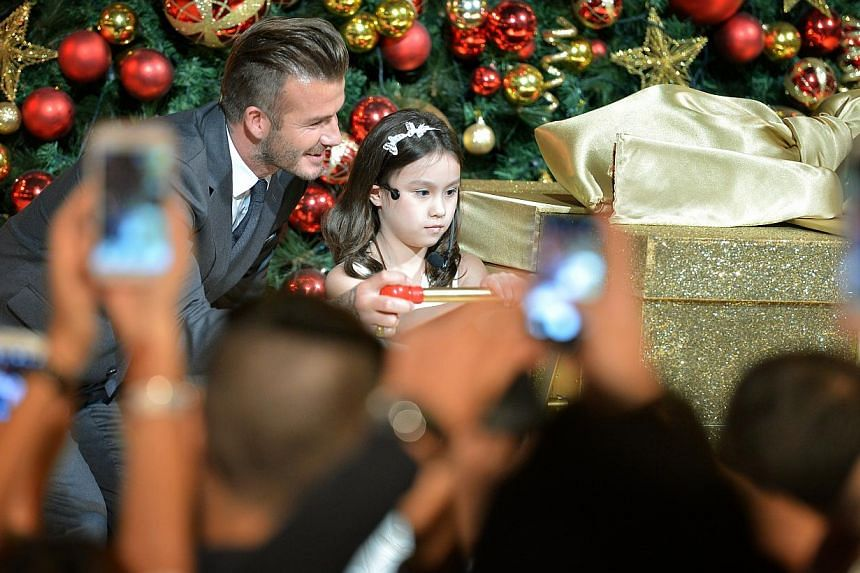 David Beckham stands at the Christmas tree with 8-year-old Kayla as they prepare to launch the Christmas light-up together for Marina Bay Sands at the skating rink. -- ST PHOTO: KUA CHEE SIONG