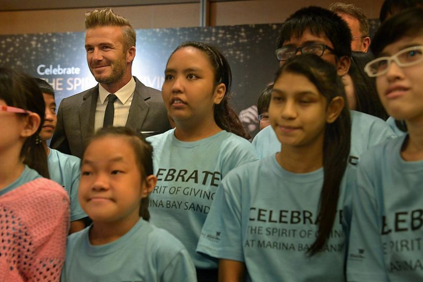 David Beckham takes pictures with a group of beneficiaries from Ang Mo Kio Family Service Centre, Association for People with Special Needs and Student Care Services, who were present at the Sands Expo and Convention Centre for the meet-and-greet ses
