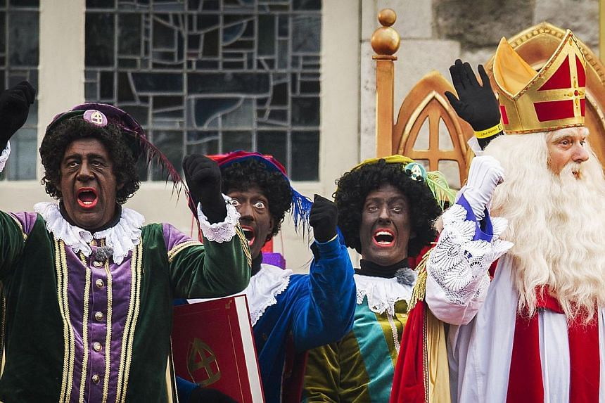 """People dressed as Saint Nicolas (right) and """"Black Peter"""" gesture during celebrations in Gouda, The Netherlands, on Nov 15, 2014.Dutch police on Saturday arrested 90 people protesting for and against the controversial """"Black Pete"""" figure at the"""