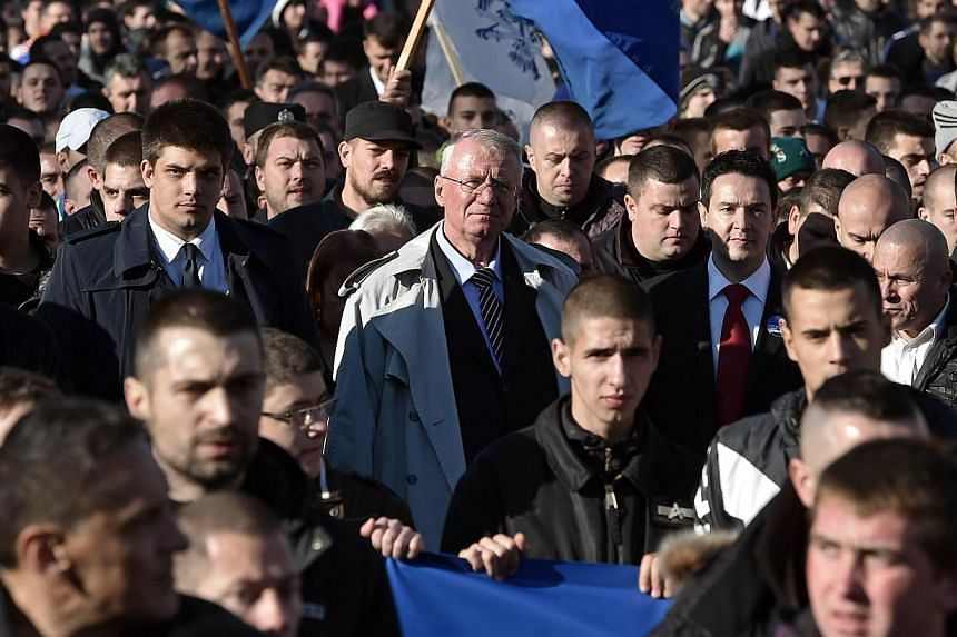 Serbian nationalist politician Vojislav Seselj walks among supporters during an anti-government rally in Belgrade on Nov 15, 2014.Some 10,000 supporters of the Serb ultranationalist Seselj, released by a UN war crimes court for cancer therapy,