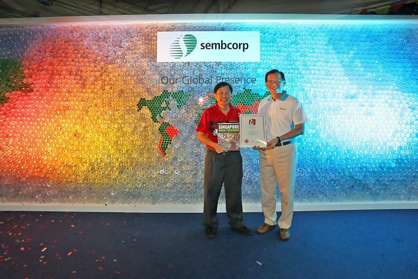 Sembcorp's Group President & CEO, Mr Tang Kin Fei, receiving the certificate for Singapore's largest wall made of recyclable plastic bottles from an official of the Singapore Book of Records.-- PHOTO: SEMBCORP INDUSTRIES