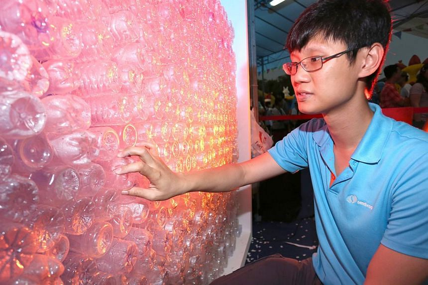 A Sembcorp employee helping to build Singapore's largest wall made of recyclable plastic bottles.-- PHOTO: SEMBCORP INDUSTRIES