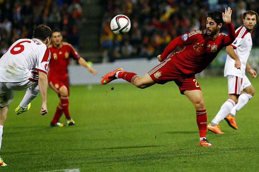Spain's Isco (second from right) tries to control the ball in front of Belarus' Sergei Balanovich (left) during their Euro 2016 Group C qualifying match in Huelva, Spain, on Nov 15, 2014. -- PHOTO: REUTERS