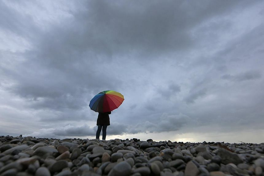 A woman protects herself under an umbrella on the beach in Nice while heavy rain and storm hit southeastern France Nov 15, 2014. Storms in southern France have left six dead, authorities said Saturday, including a mother and her two small sons after