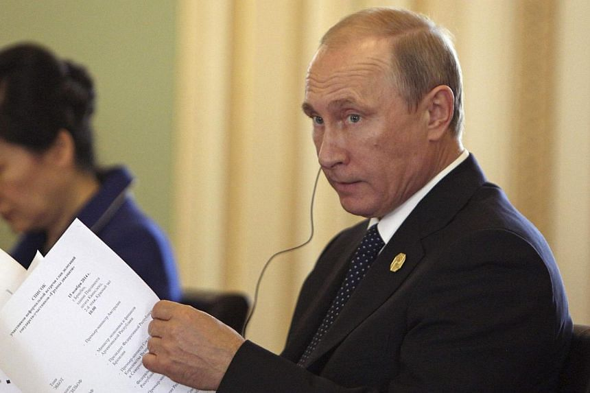 Russia's President Vladimir Putin goes through his notes before the G20 leaders in the Red Chamber at Parliament House during the G20 Leaders Summit in Brisbane on Nov 15, 2014. -- PHOTO: REUTERS