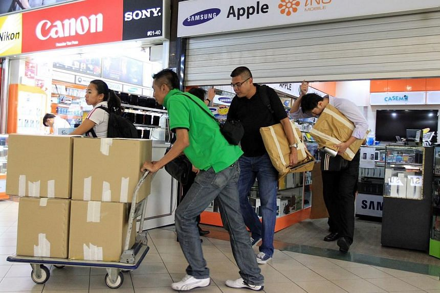Plainclothes police investigators leaving Mobile Air at Sim Lim Square with boxes and equipment. -- PHOTO: LIANHE WANBAO