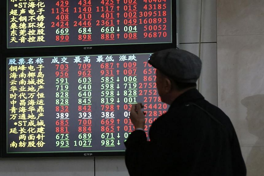 An investor looks at stock informationat a brokerage house in Shanghai on Nov 17, 2014.A daily investment quota for the Shanghai leg of a stock market scheme linking mainland China and Hong Kong exchanges was exhausted in early afternoon tradin