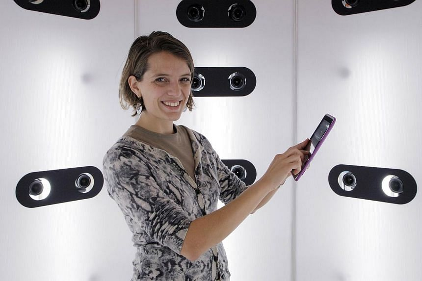 A staff member of French 3D modeling and printing company Moimee poses with a tablet in a photo booth equipped with 50 cameras, used in the process of creating silicone figurines, on Nov 13, 2014 in Paris.-- PHOTO: AFP