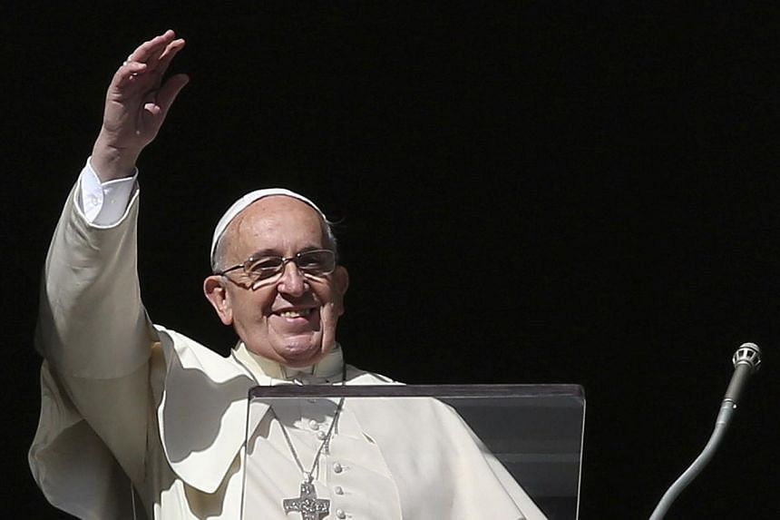 Pope Francis waves during his Sunday Angelus prayer in Saint Peter's Square at the Vatican on Nov 16, 2014. The Pope said on Monday, Nov 17, that he will visit the United States in September 2015 to take part in a Catholic Church congress on the fami