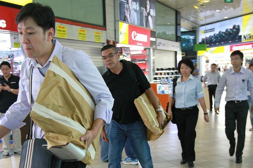 Plainclothes police investigators leaving Mobile Air at Sim Lim Square with boxes and equipment. -- PHOTO: SHIN MIN