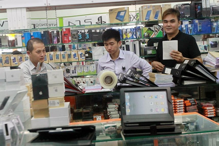 Plainclothes police investigators in Sim Lim Square retailer Mobile Air. -- PHOTO: SHIN MIN