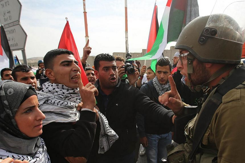 Palestinian protesters cofront Israeli soldiers in the West Bank village of Hizma, north-east of Jerusalem on Nov 14, 2014, following a demonstration to protest against Israeli authorities allowing settlers to enter the Al-Aqsa mosque compound.