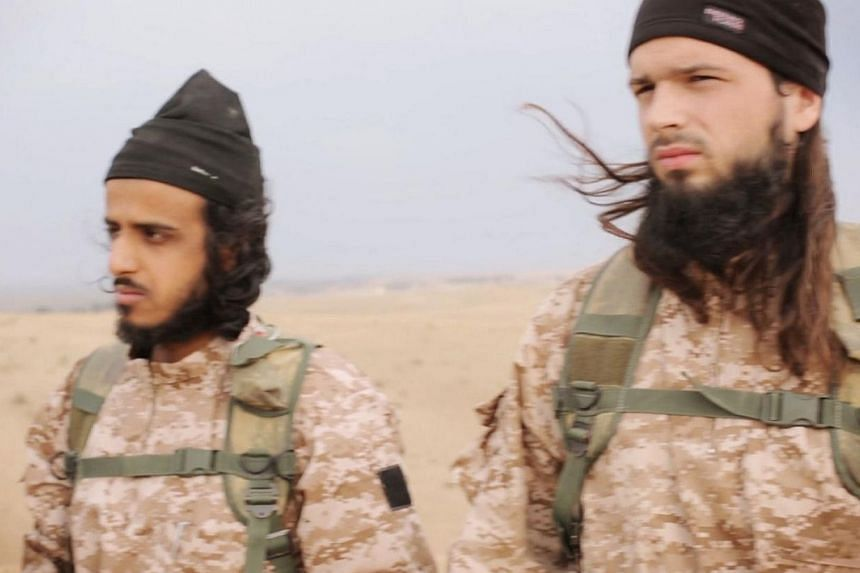 An image grab from a propaganda video released on Nov 16, 2014, by al-Furqan Media allegedly shows members of the Islamic State in Iraq and Syria (ISIS) jihadist group taking part in the beheadings of at least 18 men described as Syrian military pers