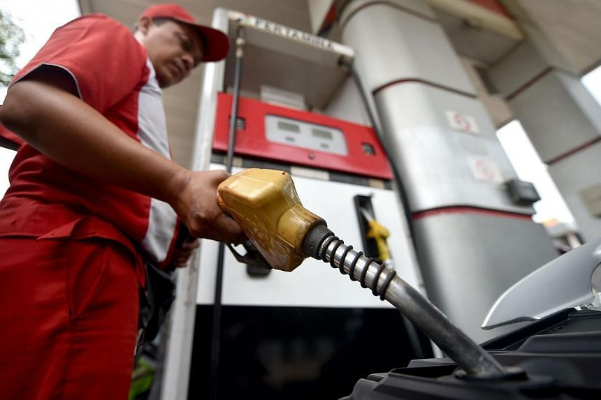 A petrol station employee fills up a vehicle with subsidised fuel in Jakarta on Nov 14, 2014. Indonesian president Joko Widodo announced a raise in subsidised fuel prices by an average Rp 2,000 per litre, effective from midnight Monday night. --