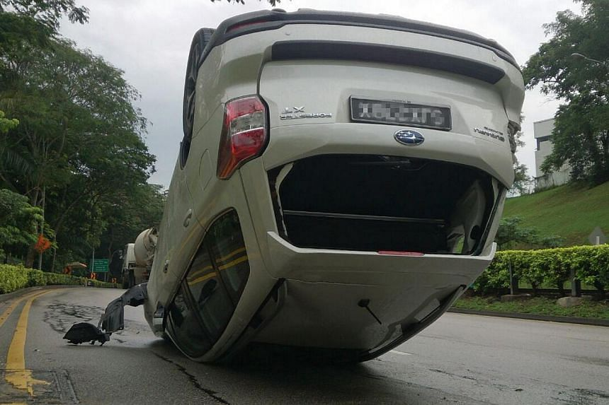 A car was found overturned on Ulu Pandan Road on Monday afternoon. -- ST PHOTO: DESMOND FOO