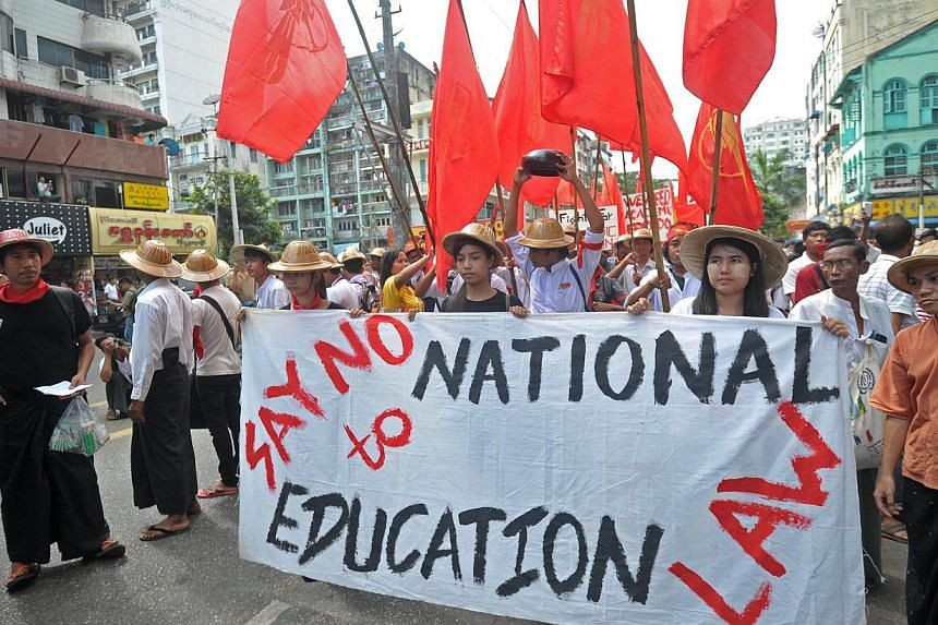 Dozens of university students march in a protest against the proposed national education bill in Yangon on Nov 17, 2014. Scores of Myanmar students rallied illegally in Yangon on Monday, Nov 17, against a new education bill they describe as unde
