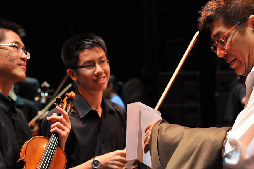ChildAid artistic director Iskandar Ismail at the opening night in 2011 with two members of the combined schools orchestra at ChildAid 2009. -- PHOTO: ST FILE