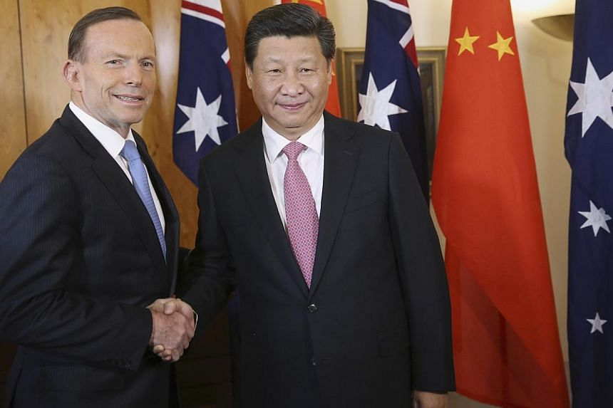 China's President Xi Jinping (right) shakes hands with Australia's Prime Minister Tony Abbott in Canberra on Nov 17, 2014. Prime Minister Tony Abbott confirmed on Monday he had concluded negotiations on a free trade deal with China. -- PHOTO: REUTERS