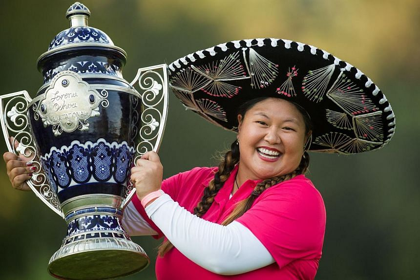 Christina Kim of the United States holds the champions trophy after her victory at the 2014 Lorena Ochoa Invitational presented by Banamex at Club de Golf Mexico in Mexico City on Nov 16, 2014. -- PHOTO: AFP