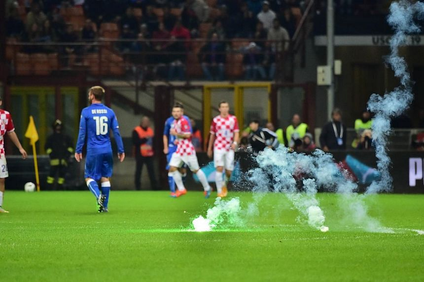 The game is interrupted as Croatia's supporters throw flares on the pitch during the Euro 2016 qualifying football match Italy vs Croatia at the San Siro stadium in Milan on Nov 16, 2014. -- PHOTO: AFP