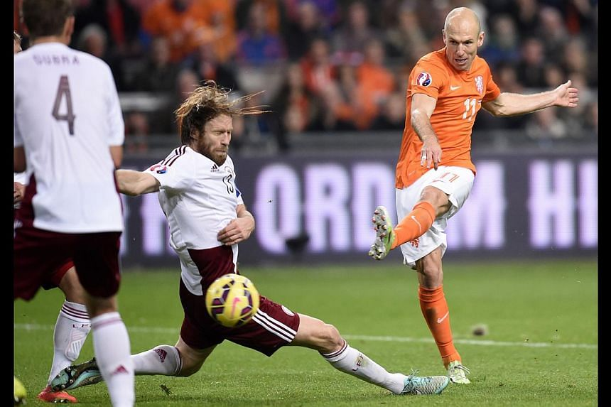 Dutch player Arjen Robben (in orange) shoots to score during the Euro 2016 qualifying round football match between the Netherlands and Latvia at the Arena Stadium, on Nov 16, 2014 in Amsterdam. -- PHOTO: AFP