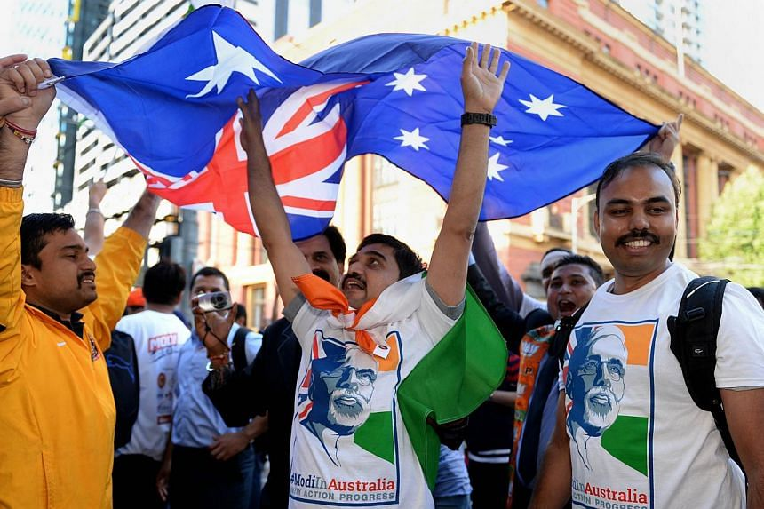 Supporters of India's Prime Minister Narendra Modi dance outside Southern Cross station in Melbourne while holding the Australian flag as they prepare to ride an overnight train with some 200 others to Sydney ahead of Modi's upcoming visit to that ci