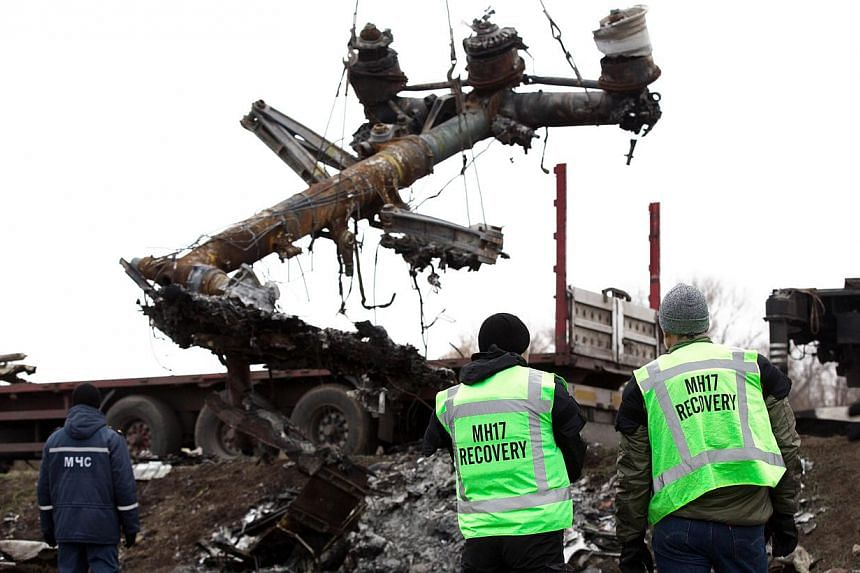 Members of the Dutch expert team watch as parts of the wreckage of the Malaysia Airlines Flight MH17 are removed and loaded on a truck at the crash site near the village of Grabove in eastern Ukraine, on Nov 16 2014. -- PHOTO: AFP
