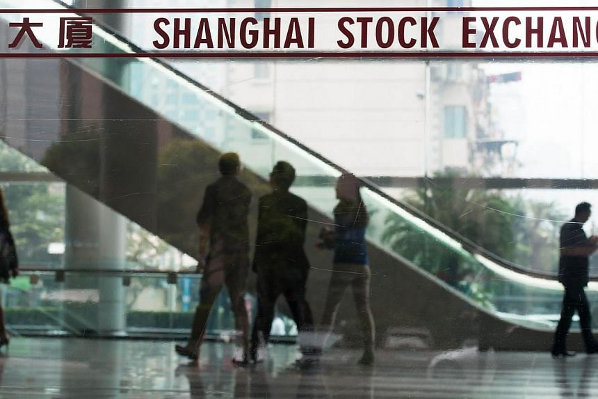 People walking inside the Shanghai Stock Exchange building in Shanghai on Oct 16. Chinese and Hong Kong shares jumped as trading opened on Monday as a landmark trading scheme linking the Shanghai and Hong Kong stock exchanges kicked off. --PHOTO: AFP