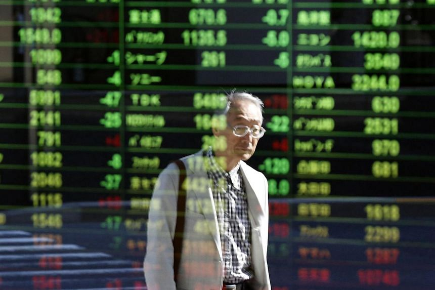 A pedestrian's image caught on an electronic board displaying stock prices in Tokyo. Asian markets mostly fell on Monday. -- PHOTO: REUTERS
