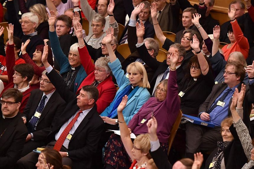 Members of the Church of England's Synod raising their hands as they formalise the vote on the consecration of women bishops in central London on Nov 17, 2014. The Church of England's governing body on Monday rubber-stamped an historic measure allowi