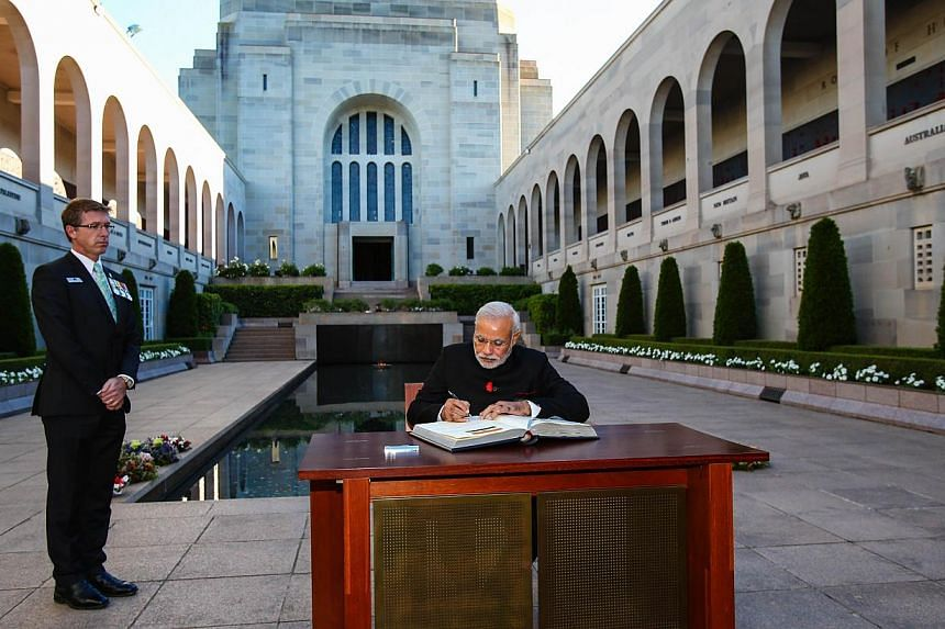 Indian Prime Minister Narendra Modi (right) signs the visitors book at the Australian War Memorial in Canberra on Nov 18, 2014. -- PHOTO: AFP