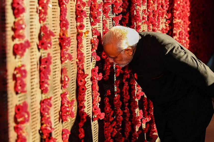 Indian Prime Minister Narendra Modi places a poppy on the wall at the Australian War Memorial in Canberra on Nov 18, 2014. -- PHOTO: AFP