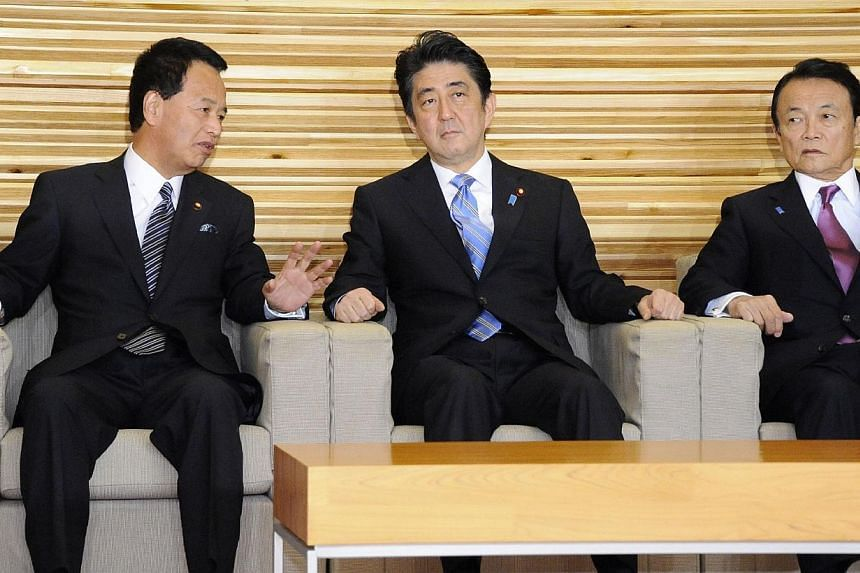 Japan's Prime Minister Shinzo Abe (centre) listens to Economic Revitalization Minister Akira Amari (left) at a cabinet meeting at the prime minister's official residence in Tokyo on Nov 18, 2014, while Finance Minister Taro Aso (right) looks on.&nbsp
