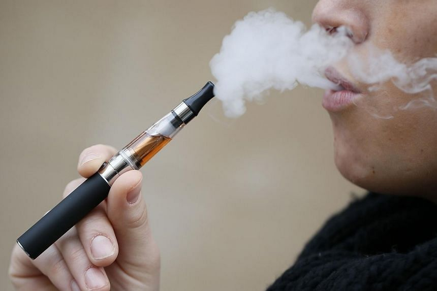 """A person smokes an electronic cigarette on March 05, 2013, in Paris.Oxford Dictionaries picked """"vape"""" - the act of smoking an e-cigarette - as their new word of the year on Tuesday, with the affectionate """"bae"""" and the more pragmatic """"contactles"""