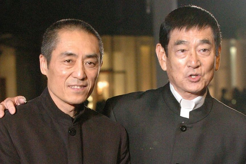"""Chinese film director Zhang Yimou (left) and Japanese actor Ken Takakura arrive on the red carpet for the opening of the 18th Tokyo International Film Festival in Tokyo on Oct 22, 2005.Ken Takakura, an actor known as """"Japan's Clint Eastwood"""" fo"""