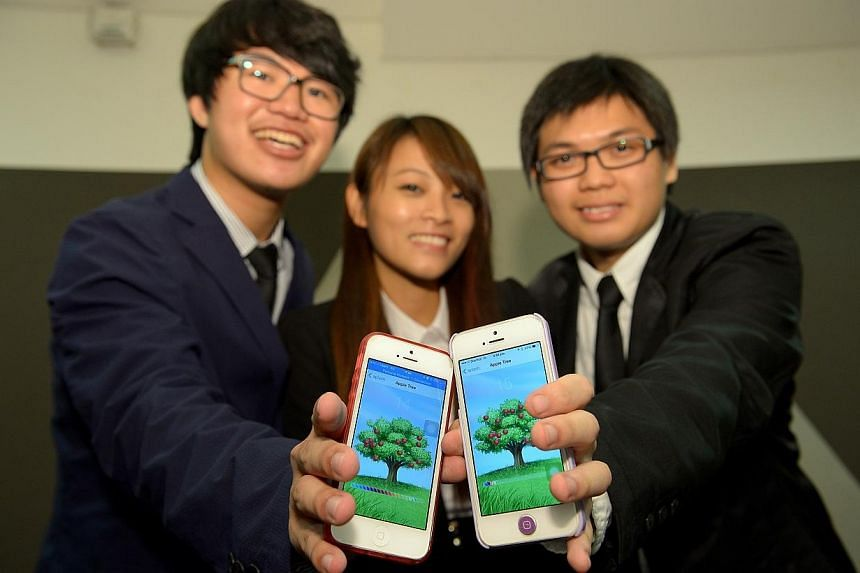 (From left) Libern Lin Yue Bin, 20, Fang LingQing, 20, and Yap Jian Le, Lester, 20, showing their award winning 'Apple Tree' apps at the Splash Awards. A team of 20-year-old Republic Polytechnic students have been awarded $30,000 to develop an a