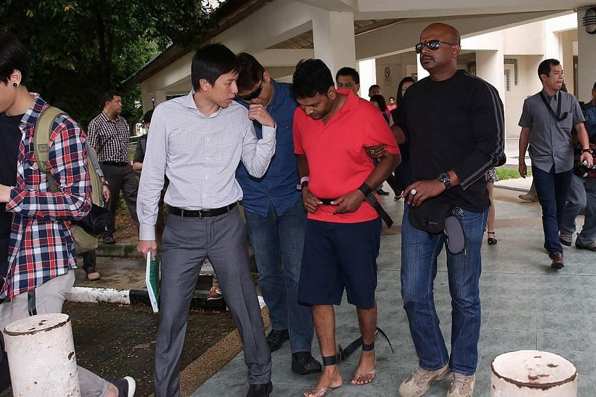 Annadurai Raman (in red), 42, one of the suspects who was charged in connection with the brazen robbery of a money changer in an open air carpark in early November is brought back to one of the crime scenes by the police at 3:15pm.A man suspect