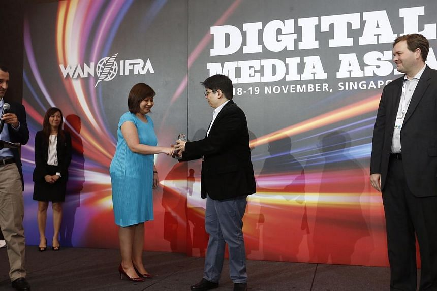 The Straits Times section pages editor Ong Hwee Hwee receiving the bronze award for Best Mobile Service at Digital Media Asia at Orchard Hotel on Nov 18, 2014. Presenting the award to her is Mr J.V. Rufino, director of mobile and books at the Philipp