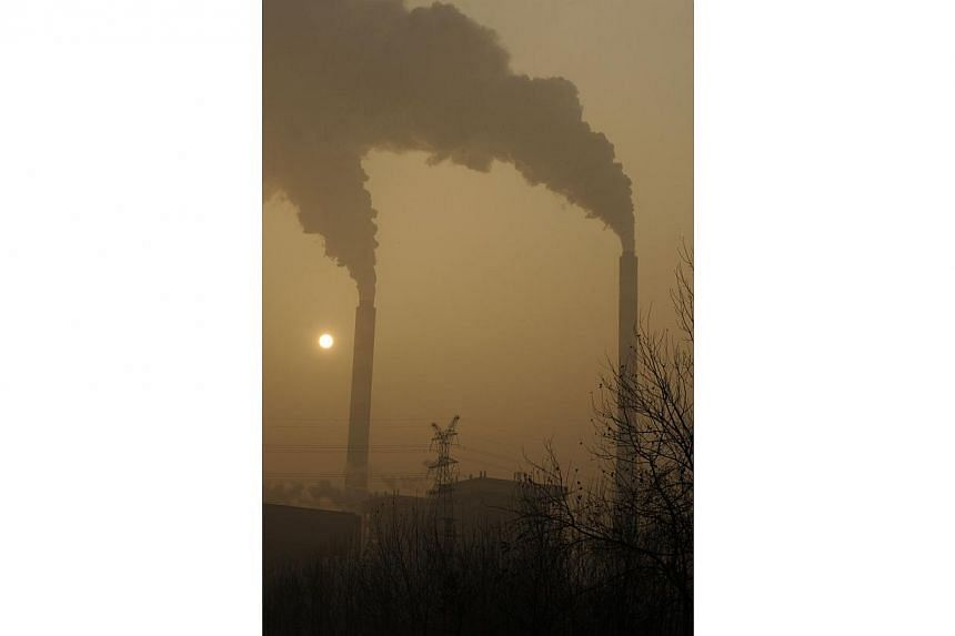 """A file photo taken on Dec 8, 2009, shows smoke belching from a coal powered power plant on the outskirts of Linfen, in China's Shanxi province, regarded as one of the cities with the worst air pollution in the world.China needs to hit its """"peak"""