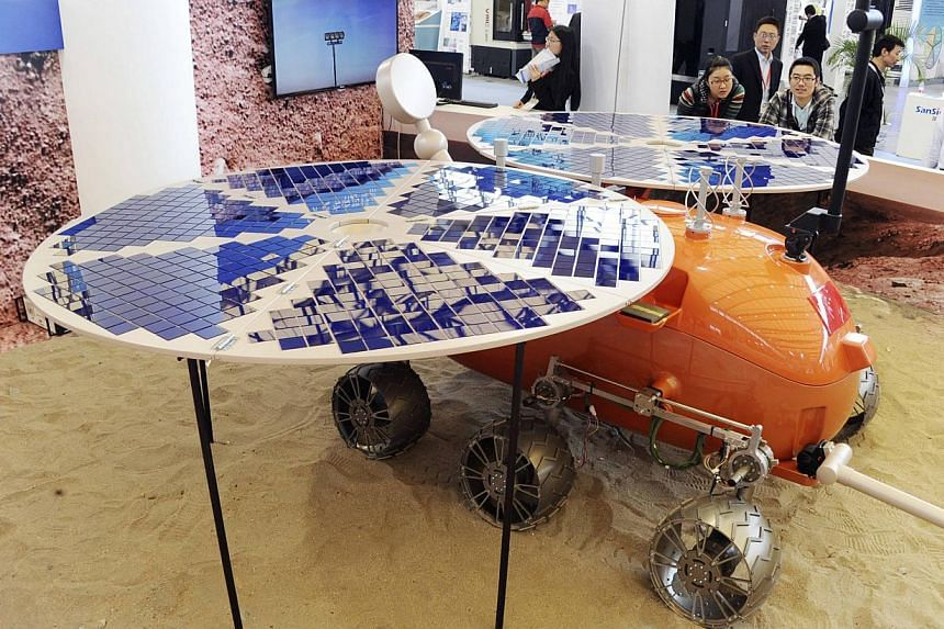 """Visitors look at a prototype model of a Mars rover, which was designed and built in China, on display at the China International Industry Fair in Shanghai, on Nov 4, 2014.Chinese scientists are planning to launch a Mars rover """"around 2020"""", sta"""