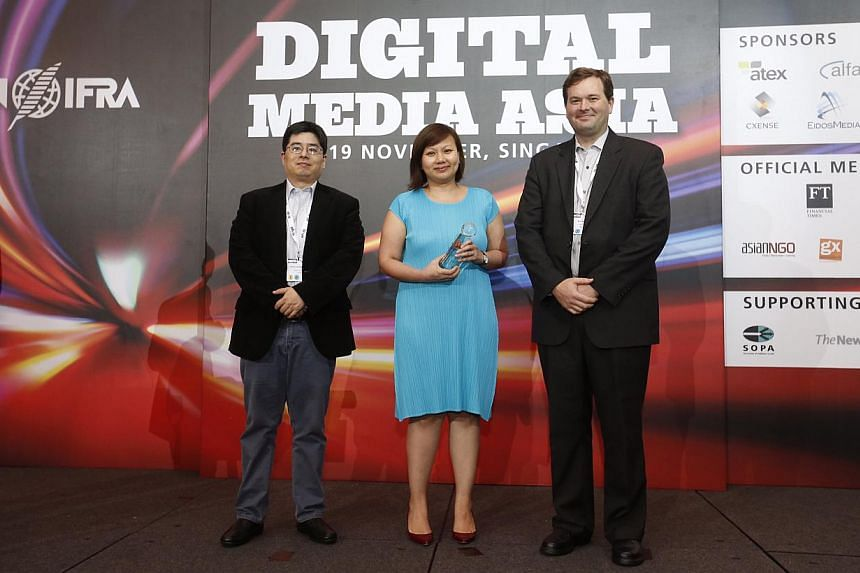 The Straits Times section pages editor Ong Hwee Hwee with the bronze award for Best Mobile Service at Digital Media Asia at Orchard Hotel on Nov 18, 2014. -- ST PHOTO: KEVIN LIM